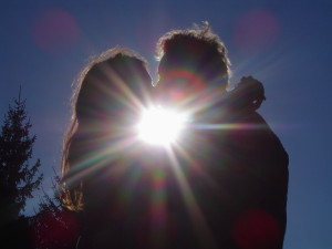 A pair of lovers are kissing each other in direct sunlight.